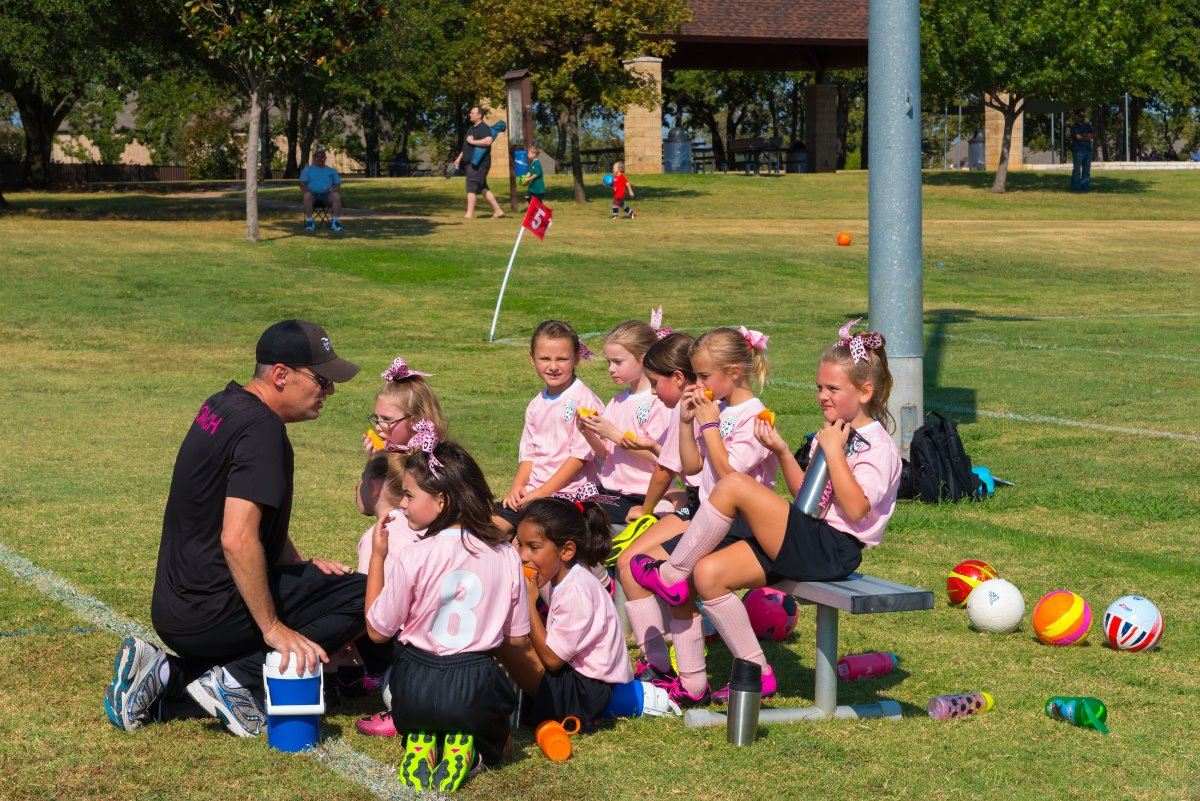 Youth Girls Soccer Team sitting on bench