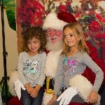 Two Little Girls Sitting on Santa's Lap for a Picture