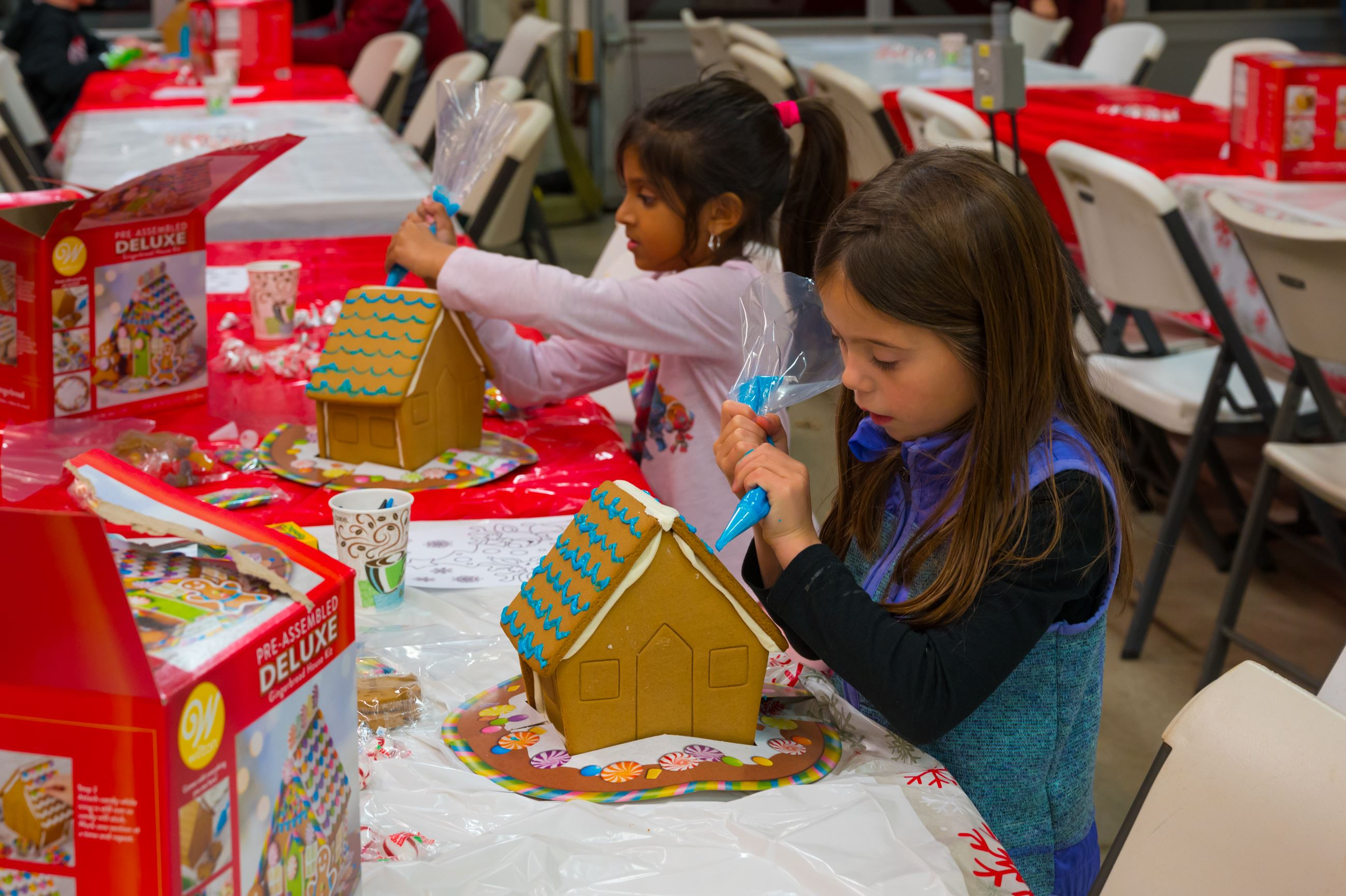 Two girls decorating a gingerbread house