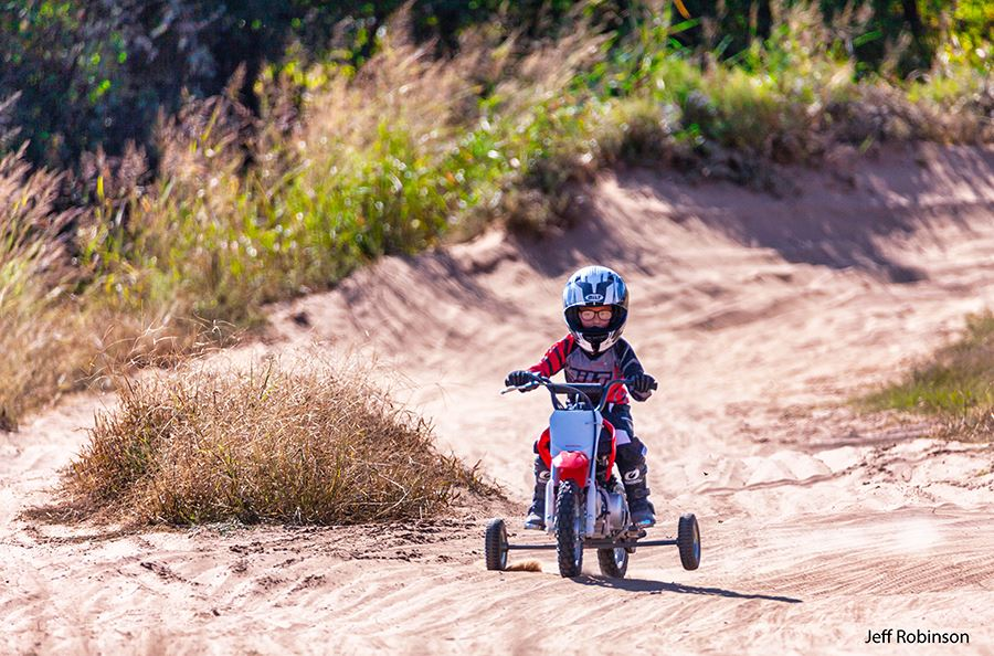 Child riding moto x bike with training wheels