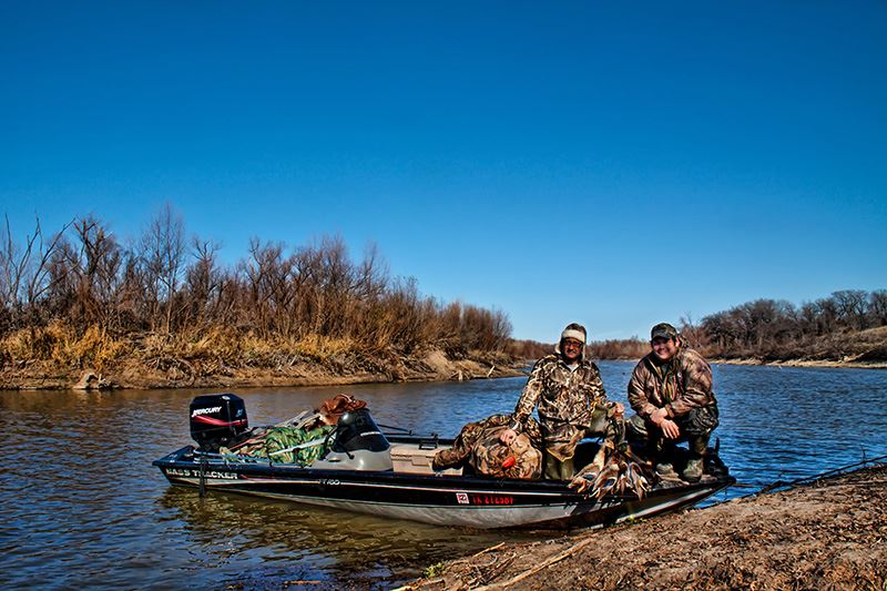 duck hunters on boat with ducks