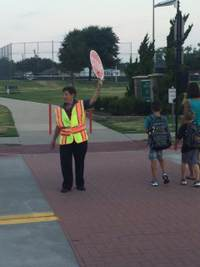 Crossing Guard Stopping Traffic to let Children Cross