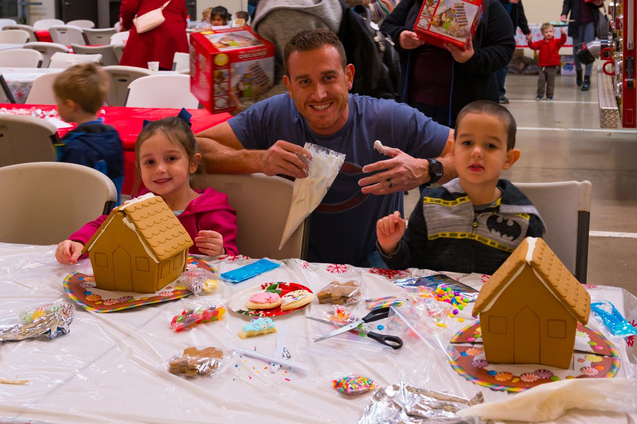 Father and Two Children Decorating Gingerbread Houses