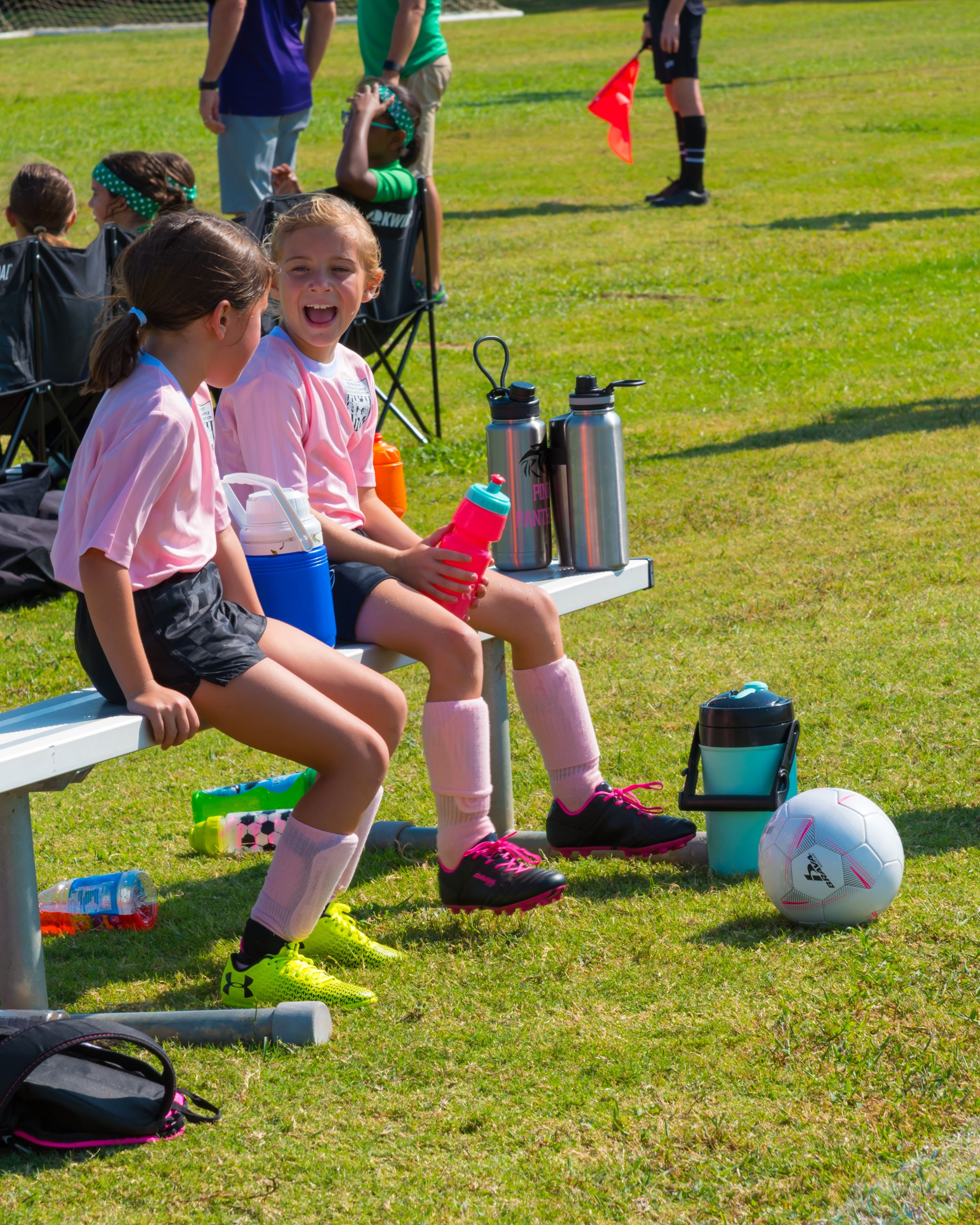 Two Girls Sitting on a Soccer Bench